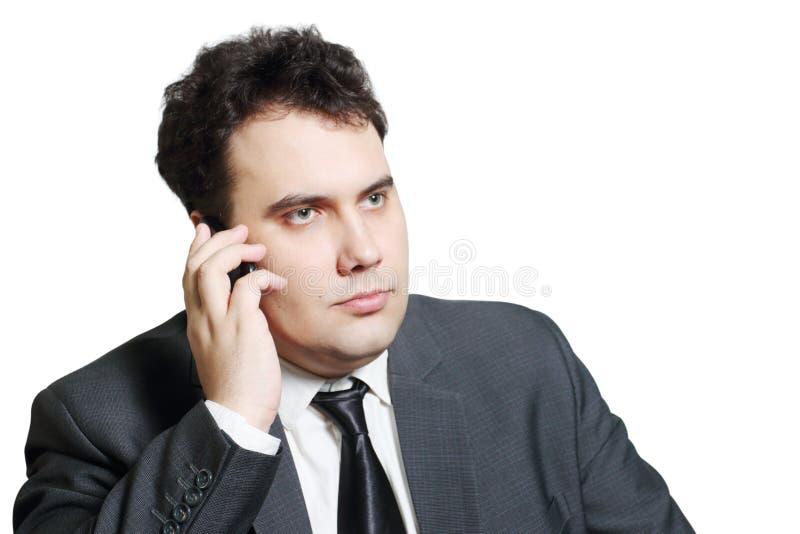 Poważny młody biznesmen w kostiumów wezwaniach telefonem komórkowym obrazy stock