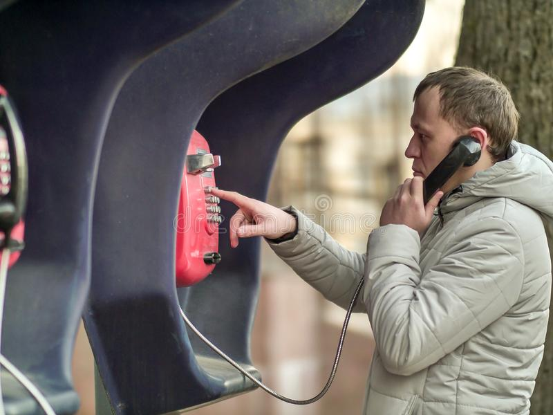 Poważny młody człowiek dzwoni czerwonym ulicznym payphone zdjęcia stock