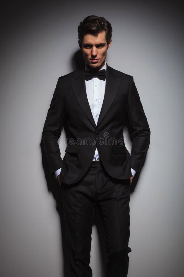 Poważny młody człowiek jest ubranym smoking pozycję z rękami w kieszeniach zdjęcie stock