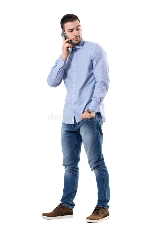 Poważny młody skeptical biznesmen opowiada na telefonie przyglądającym z powrotem zdjęcia stock