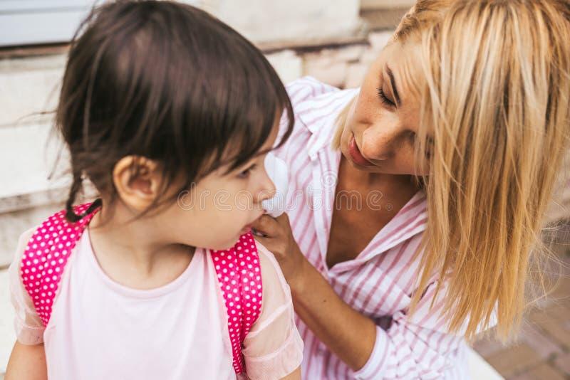 Poważny matki i ucznia córki narządzania plecak iść preschool obsiadanie na schodkach dom plenerowy związek obraz stock