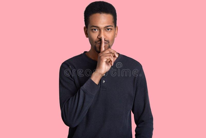 Poważny murzyn trzyma pierwszego planu palec nad wargami, demonstruje shush gest, ubierającego w przypadkowej bluzie, mówi tajną  obraz stock