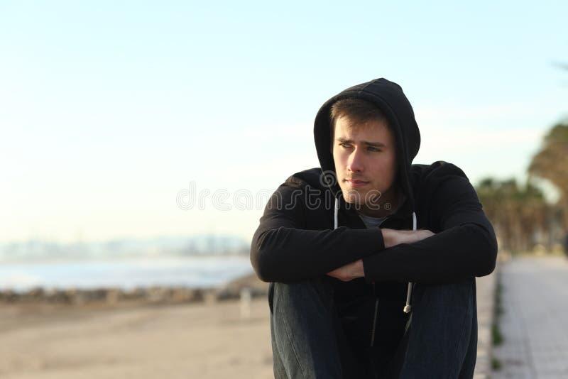Poważny nastoletni chłopak patrzeje daleko od na plaży zdjęcia stock
