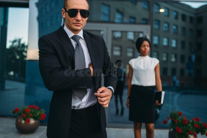 Poważny ochroniarz w kostiumu, okularach przeciwsłonecznych i earpiece, zdjęcie stock
