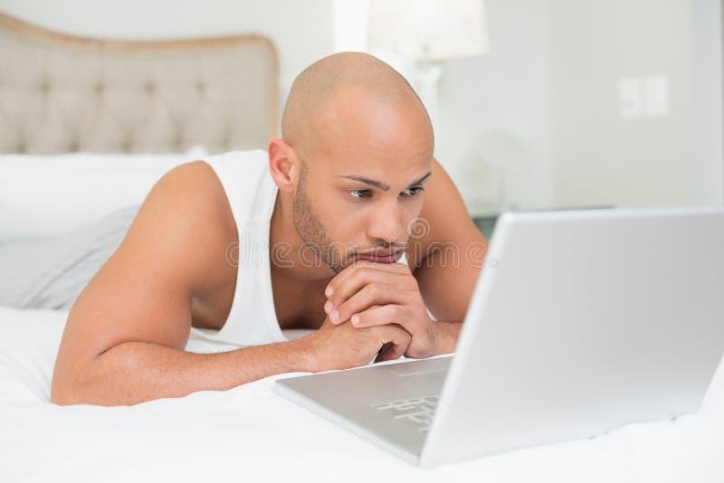 Poważny przypadkowy łysy mężczyzna używa laptop w łóżku obrazy stock