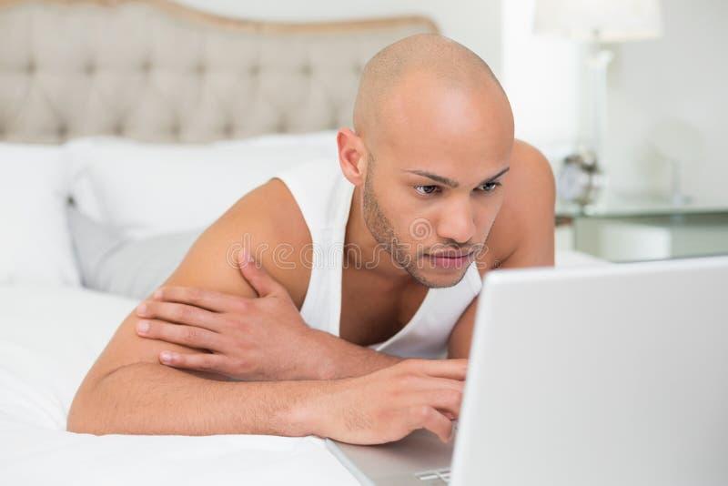 Poważny przypadkowy łysy mężczyzna używa laptop w łóżku zdjęcia royalty free