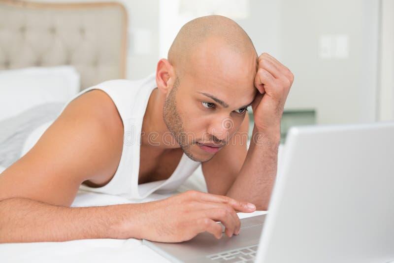 Poważny przypadkowy łysy młody człowiek używa laptop w łóżku zdjęcia royalty free