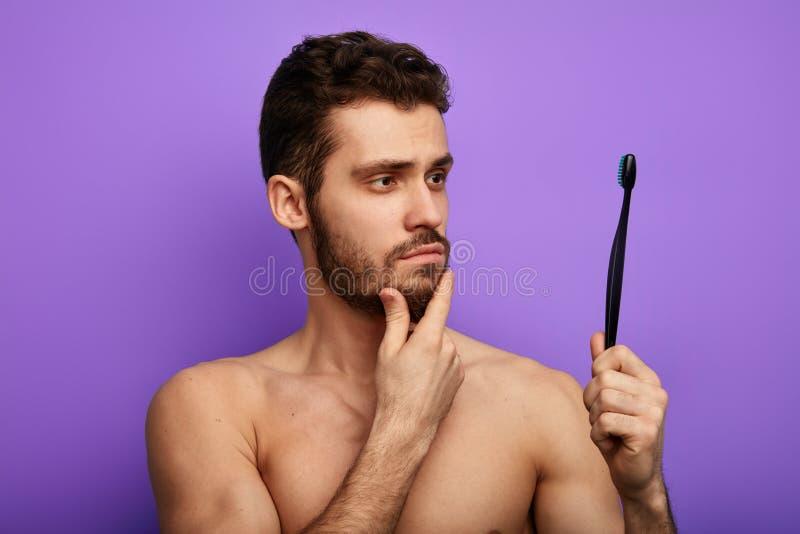 Powa?ny rozwa?ny m?ody cz?owiek trzyma toothbrush i patrze? je zdjęcie royalty free