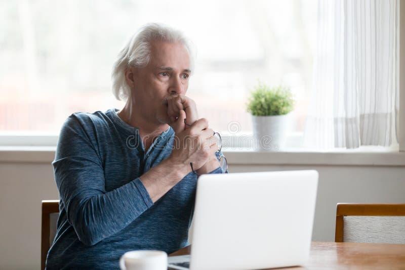 Poważny rozważny starszego mężczyzna przyglądający oddalony główkowanie problem s zdjęcia royalty free
