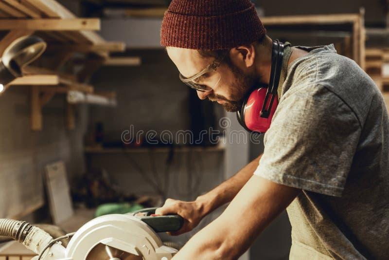 Poważny rzemieślnik używa kurendę zobaczył fotografia stock