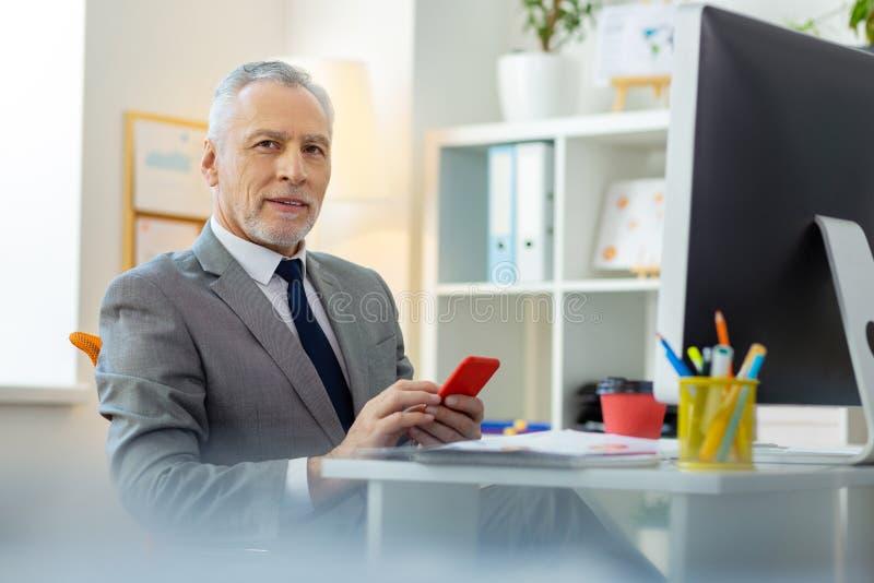 Poważny siwowłosy mężczyzna niesie czerwonego smartphone z ciemnymi oczami obraz royalty free