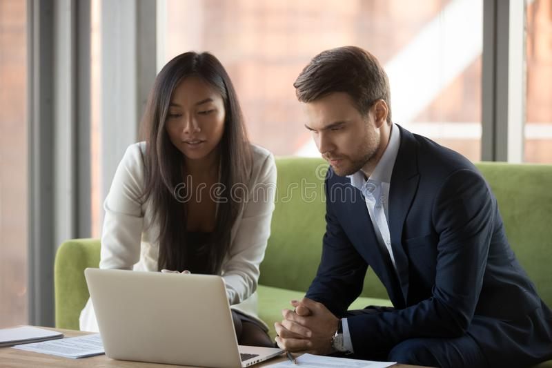 Poważny skupiający się azjatykci bizneswoman i caucasian biznesmen patrzeje laptop zdjęcie stock