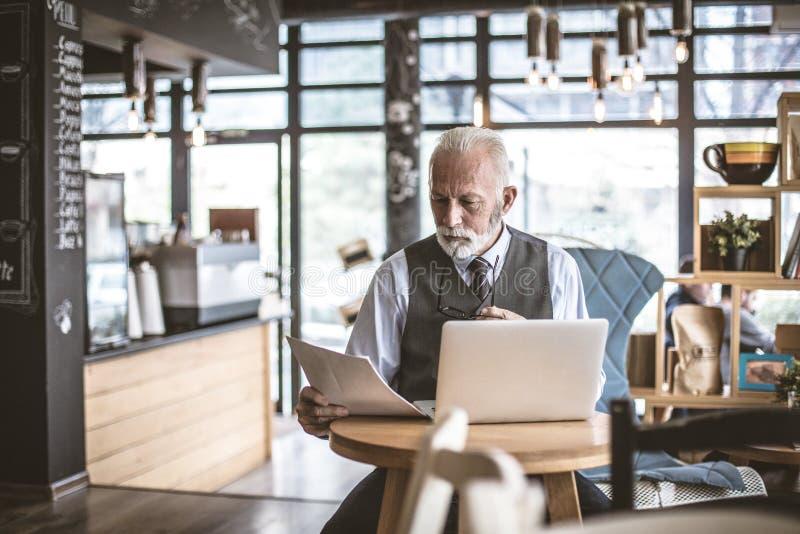 Poważny starszy biznesmen przy kawiarnią, pracuje obraz royalty free
