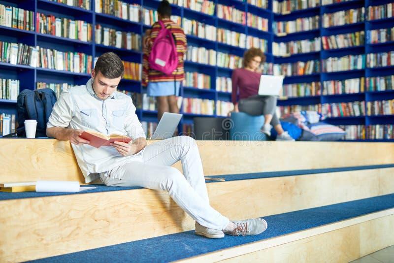 Poważny uczeń robi do domu zadaniu w bibliotece obrazy royalty free