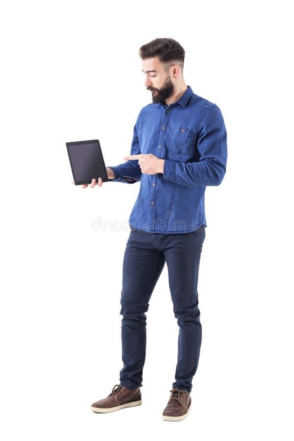 Poważny ufny biznesowy mężczyzna wskazuje palec przy pastylką i przedstawia ochraniacza zastosowanie obrazy stock