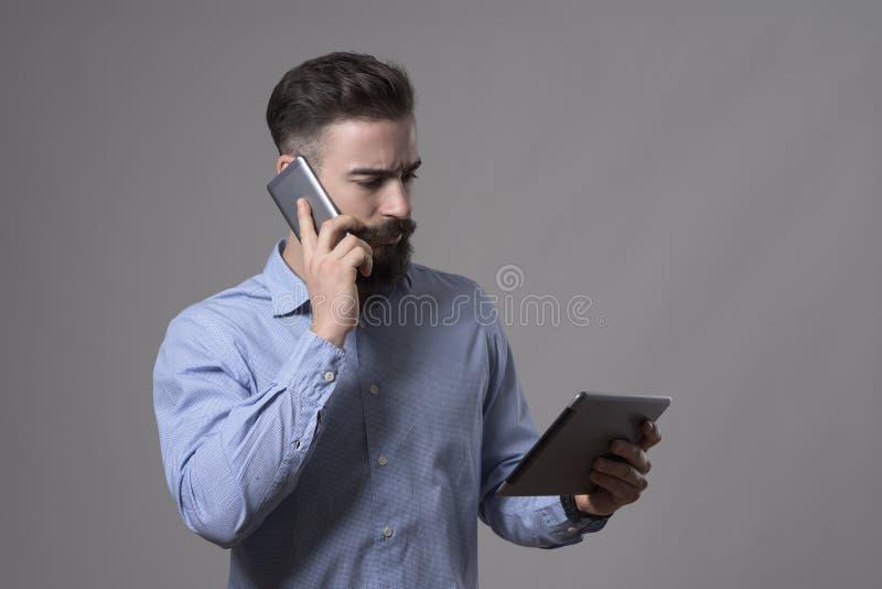 Poważny ufny młody biznesowy mężczyzna opowiada na telefonie i patrzeje pastylka komputer fotografia royalty free