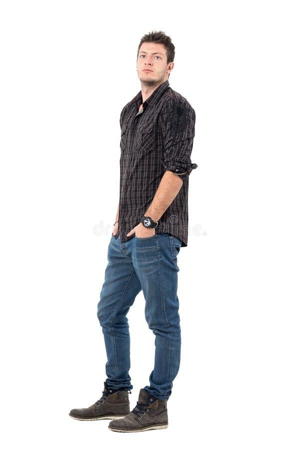 Poważny ufny młody przypadkowy mężczyzna w cajgach i koszulowej patrzeje kamerze zdjęcie royalty free