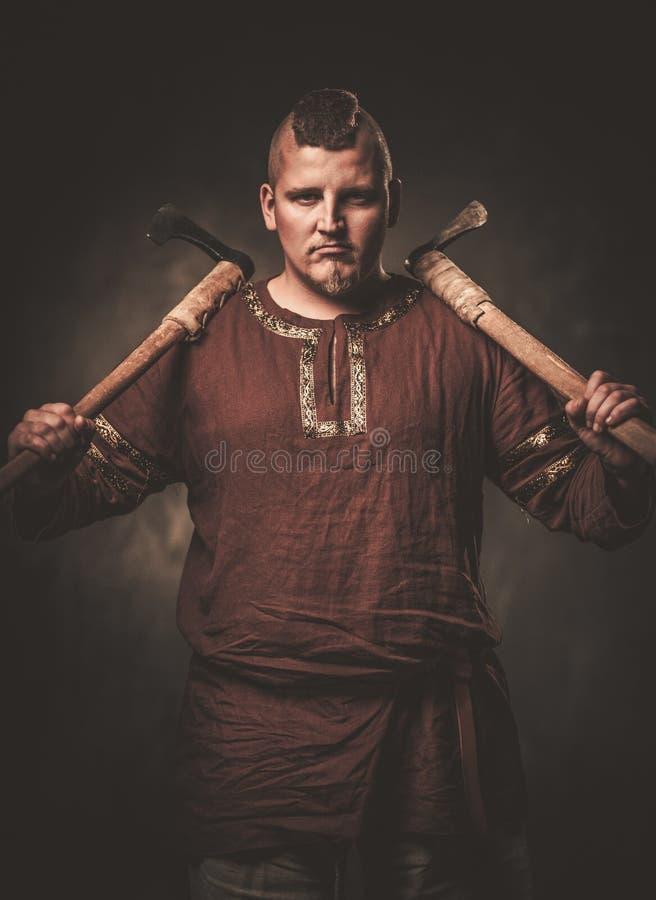 Poważny Viking z cioskami w wojownika tradycyjnych ubraniach, pozuje na ciemnym tle zdjęcie stock