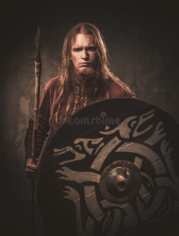 Poważny Viking z dzidą w wojownika tradycyjnych ubraniach, pozuje na ciemnym tle obrazy royalty free