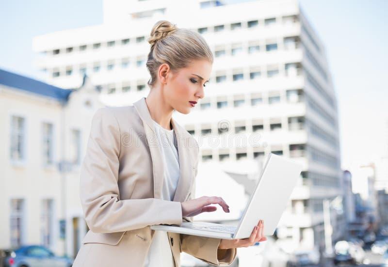 Poważny wspaniały bizneswomanu mienia laptop fotografia stock