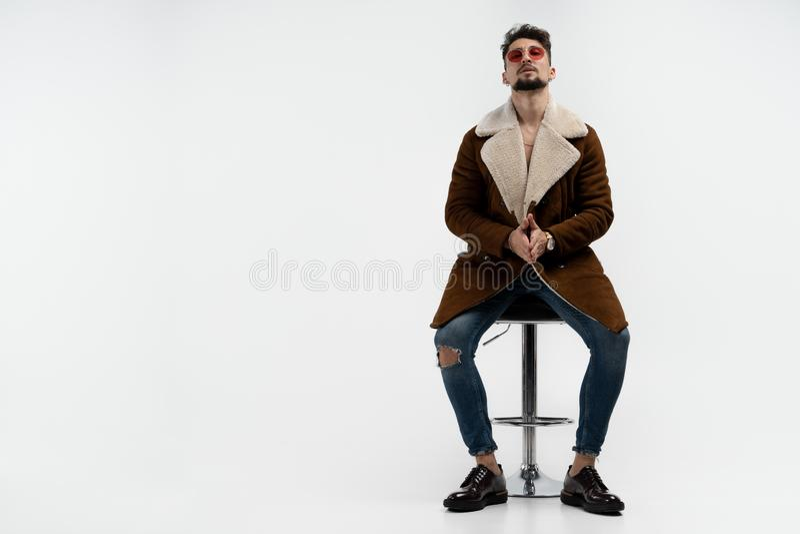 Powa?ny brodaty m??czyzna siedzi na pr?towej stolec w przypadkowych eleganckich odzie?owych i czerwonych okularach przeciws?onecz zdjęcia royalty free