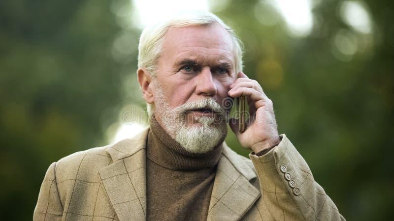 Powa?ny starszy biznesmen opowiada na telefonie, z?a wiadomo??, technologia komunikacyjna fotografia royalty free