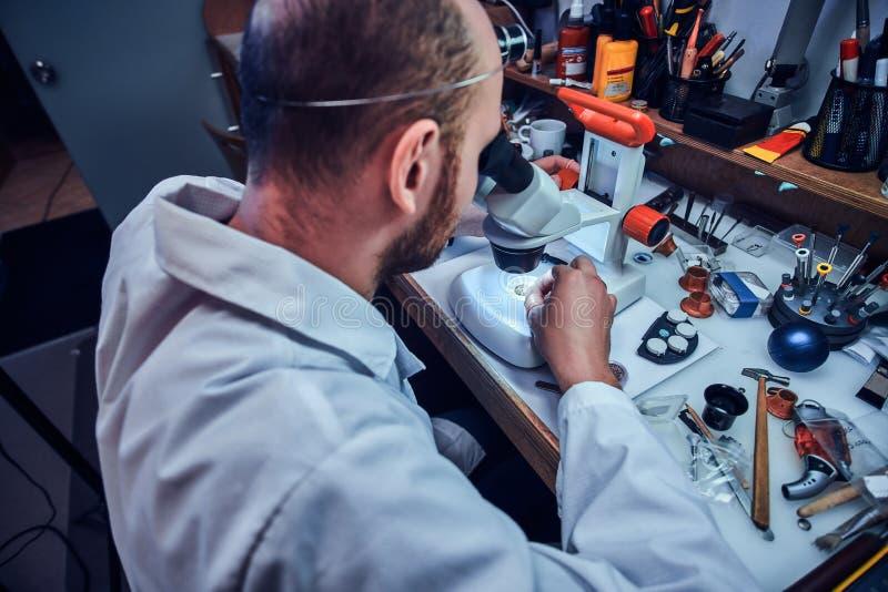 Powa?ny zegarmistrz naprawia cutomer rozkaz przy jego sw?j naprawiania studiiem obraz stock