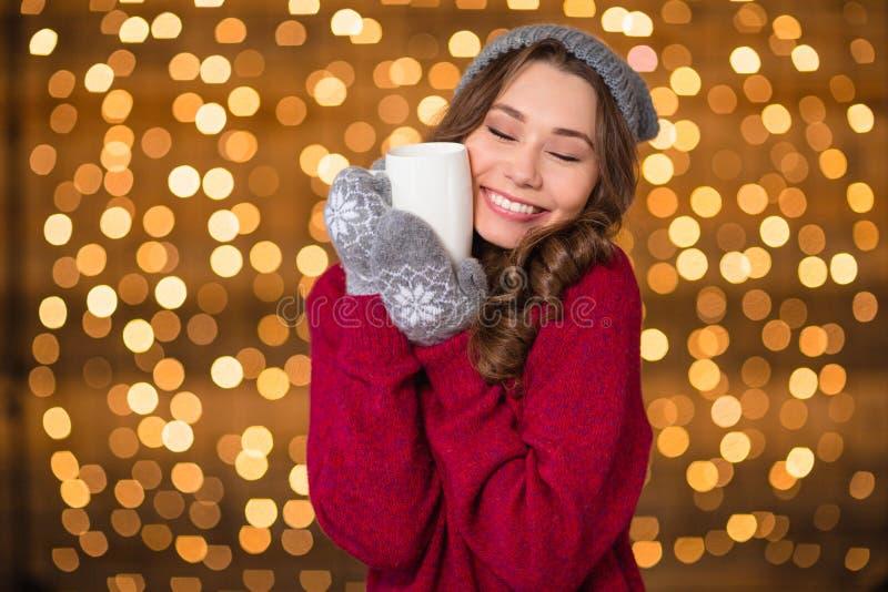 Powabna śliczna dama ściska filiżankę ciepła herbata i ono uśmiecha się zdjęcia royalty free