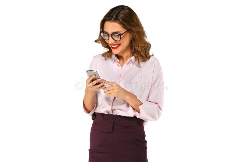 Powabna biznesowa kobieta patrzeje telefon komórkowego obraz stock