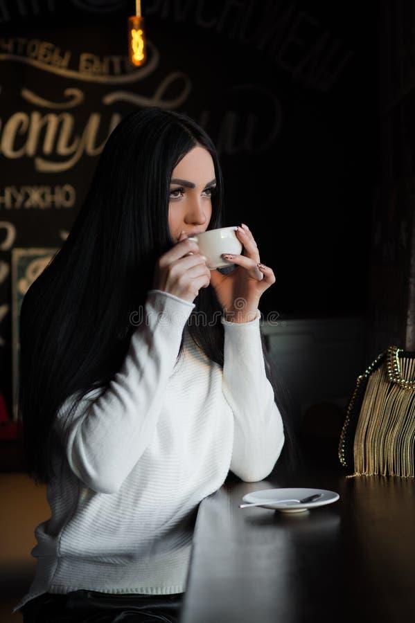 Powabna brunetka w kawiarni pije kawę obraz royalty free