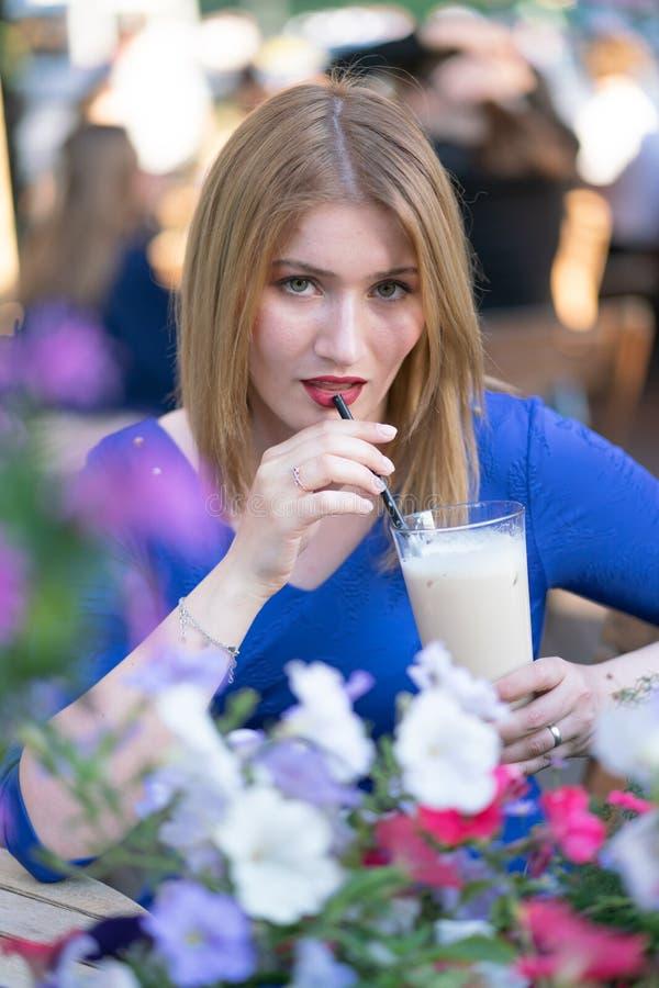 Powabna caucasian blondynki dziewczyna w b??kitnym smokingowym obsiadaniu przy sto?em w miasta cukierniany czekaniu i samotnym fotografia royalty free