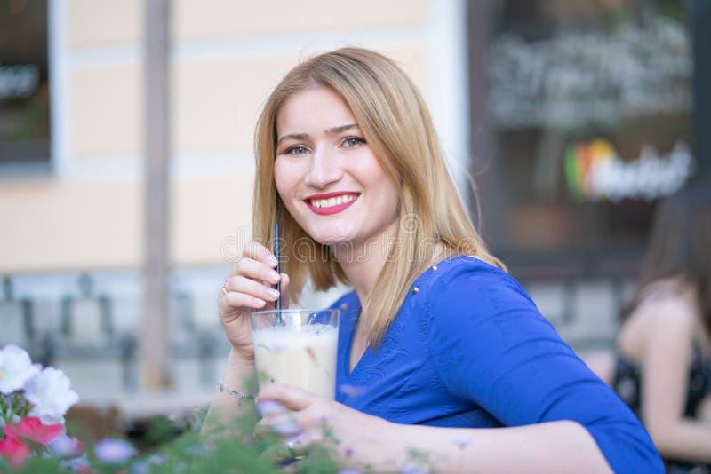 Powabna caucasian blondynki dziewczyna w b??kitnym smokingowym obsiadaniu przy sto?em w miasta cukierniany czekaniu i samotnym zdjęcia royalty free