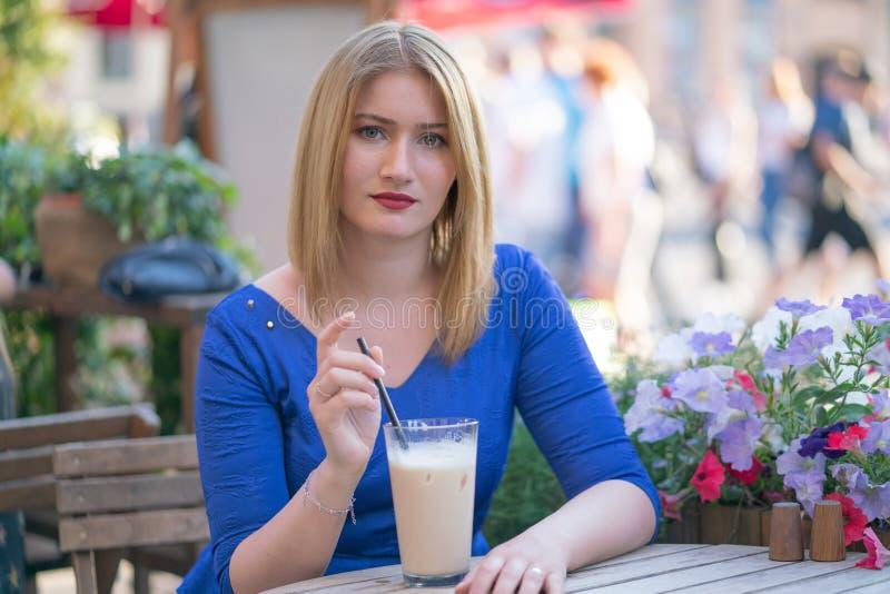Powabna caucasian blondynki dziewczyna w b??kitnym smokingowym obsiadaniu przy sto?em w miasta cukierniany czekaniu i samotnym obraz stock