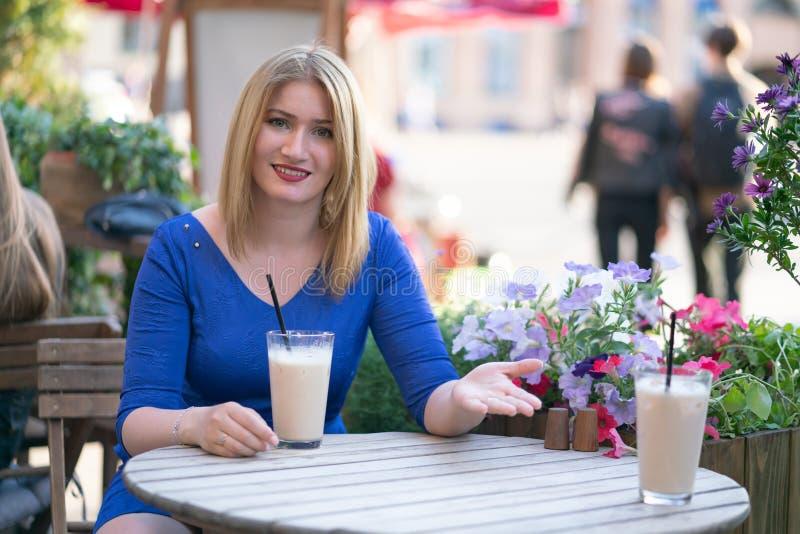 Powabna caucasian blondynki dziewczyna w b??kitnym smokingowym obsiadaniu przy sto?em w miasta cukierniany czekaniu i samotnym zdjęcie royalty free