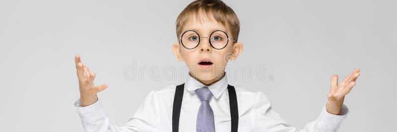 Powabna chłopiec w białej koszula, suspenders, krawacie i światło cajgów stojakach na szarym tle, Chłopiec rozprzestrzenia jego r obraz royalty free