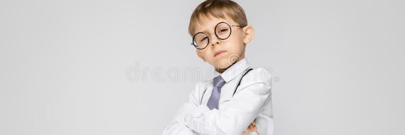 Powabna chłopiec w białej koszula, suspenders, krawacie i światło cajgów stojakach na szarym tle, Chłopiec składał jego ręki obraz royalty free