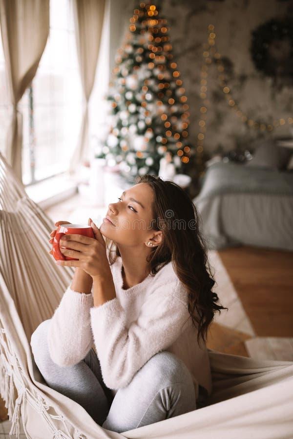 Powabna ciemnowłosa dziewczyna ubierał w beżowym pulowerze i spodnia trzymają czerwonego filiżanki obsiadanie dekorują w hamaku w zdjęcia royalty free