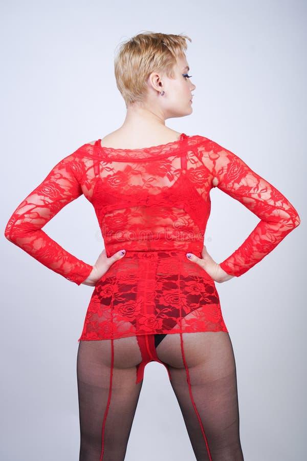 Powabna dorosła blondynki dziewczyna z krótkim włosy i curvy ciałem pozuje w seksownej koronkowej bluzce czarnym klasycznym rajst zdjęcie royalty free