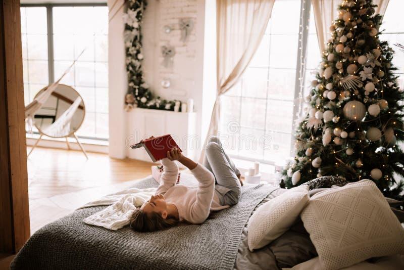 Powabna dziewczyna ubierająca w białych spodniach i pulowerze czyta książkę liying na łóżku z szarą koc, białymi poduszkami i a, zdjęcia royalty free