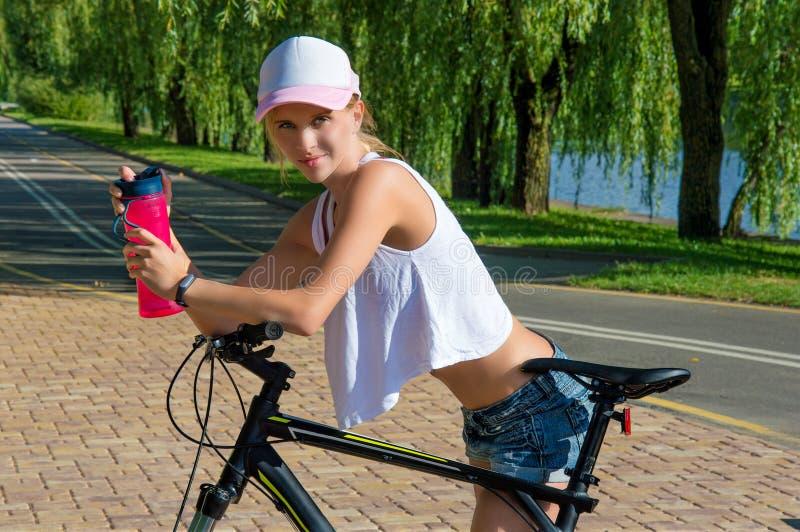 Powabna dziewczyna w parku na rowerze zdjęcia royalty free