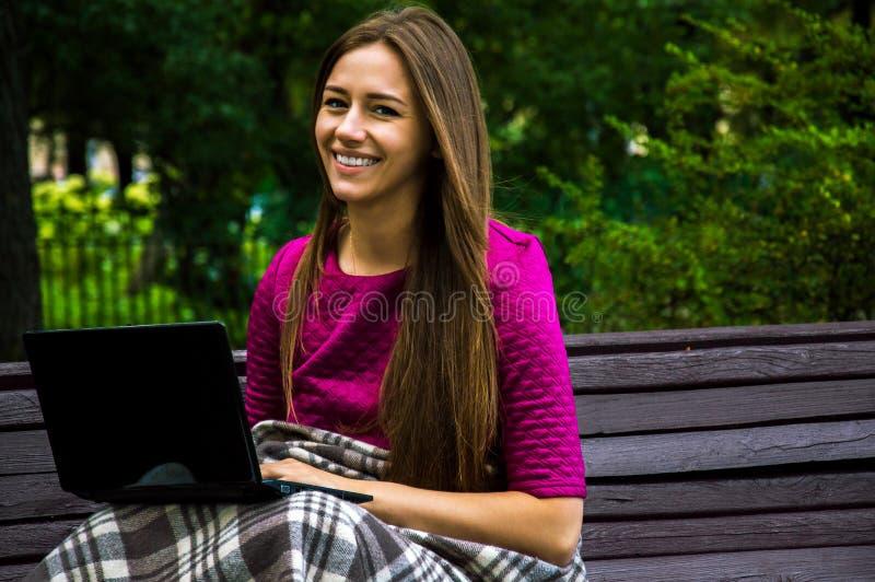 Powabna dziewczyna w purpurowym smokingowym obsiadaniu na ławce w parku w zdjęcie royalty free
