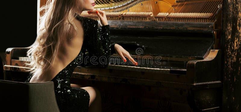 Powabna dziewczyna w wieczór sukni bawić się starego Niemieckiego pianino widok z powrotem zdjęcie stock