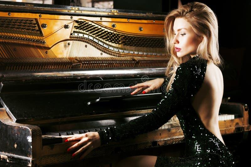 Powabna dziewczyna w wieczór sukni pozuje blisko starego Niemieckiego pianina widok z powrotem zdjęcie stock