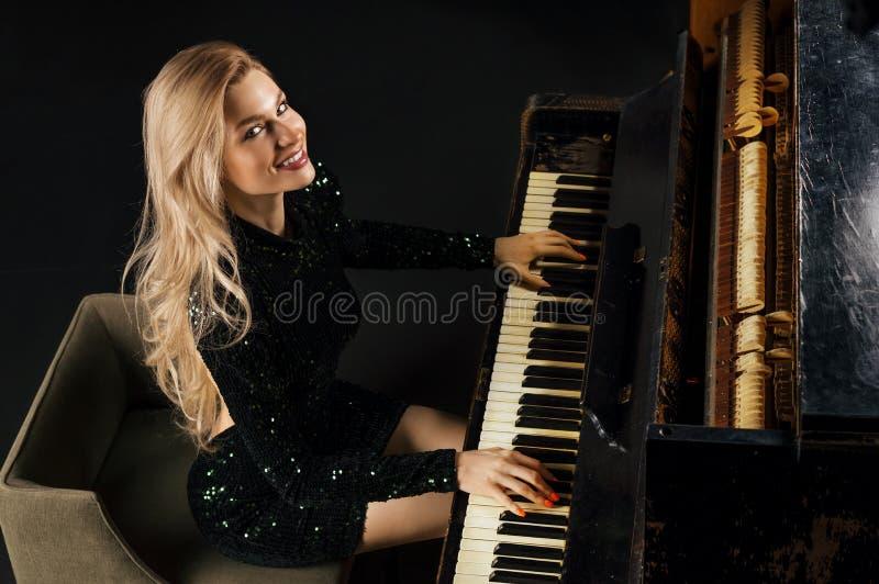 Powabna dziewczyna w wiecz?r sukni bawi? si? starego Niemieckiego pianino na widok fotografia stock