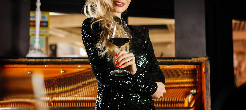 Powabna dziewczyna w wiecz?r sukni cieszy si? muzyk? i pije czerwone wino obraz royalty free