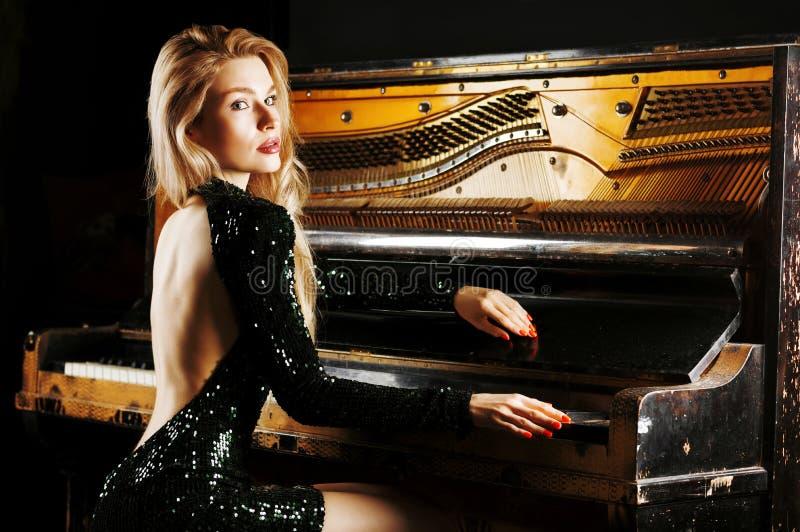 Powabna dziewczyna w wiecz?r sukni pozuje blisko starego Niemieckiego pianina widok z powrotem zdjęcia stock