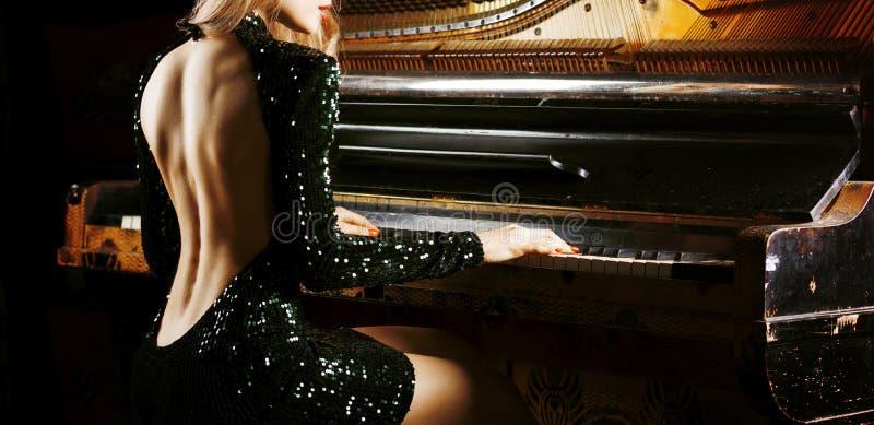 Powabna dziewczyna w wiecz?r sukni pozuje blisko starego Niemieckiego pianina widok z powrotem obraz royalty free