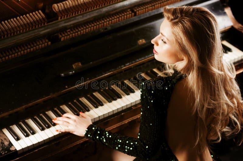Powabna dziewczyna w wiecz?r sukni pozuje blisko starego Niemieckiego pianina widok z powrotem obraz stock