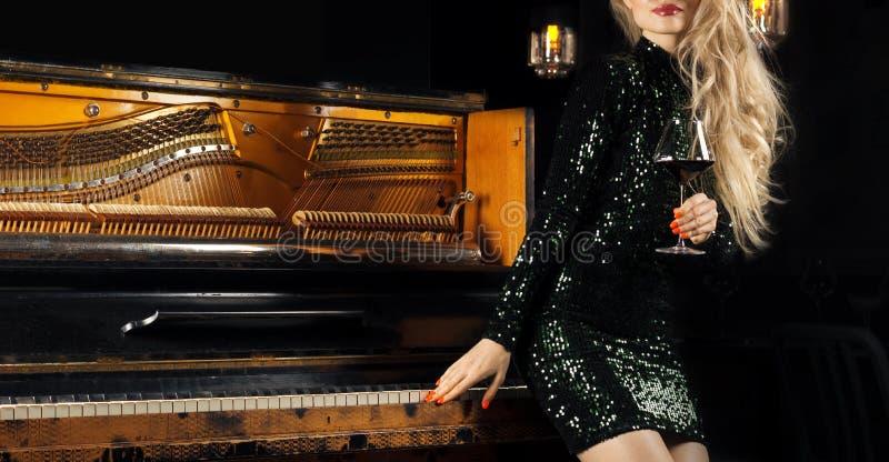 Powabna dziewczyna w zielonej wieczór sukni pozuje z szkłem wino w jej ręce blisko retro pianina zdjęcia royalty free