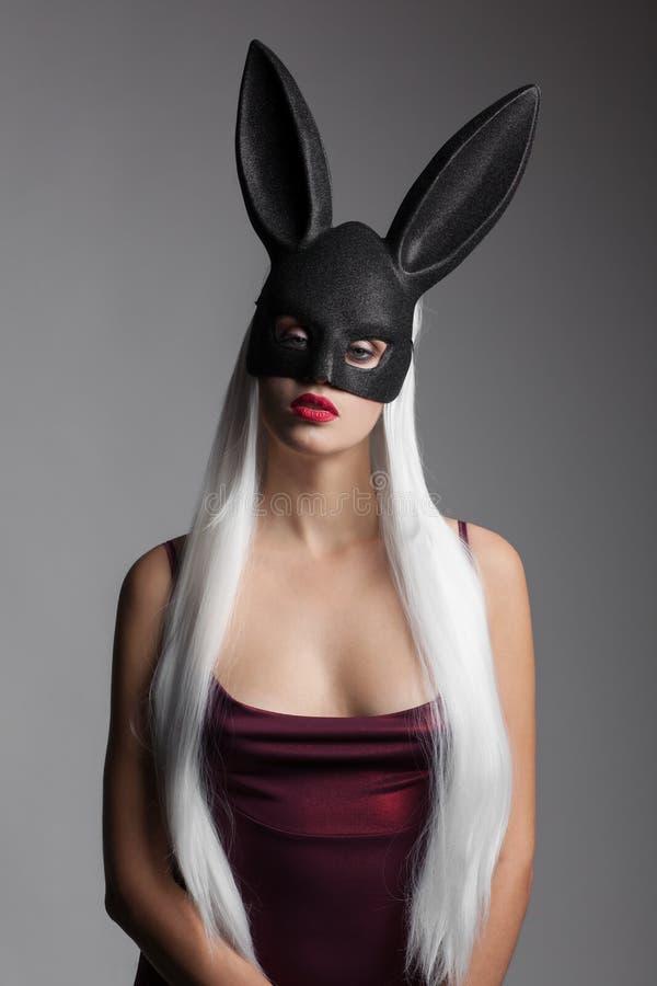 Powabna dziewczyna z długim prostym białym włosy i czarna królik maska na jej głowie obrazy stock
